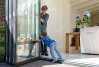 Mann und Junge öffnen Glas-Faltwand