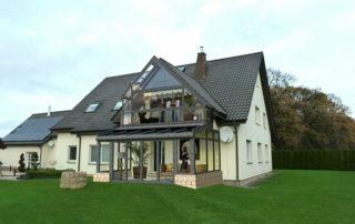 Bild eines Einfamilienhauses mit eingearbeiteter Wintergarten-Ansicht