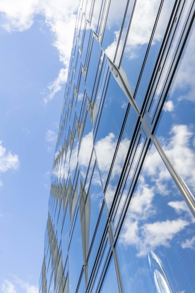 Gläserne Hausfassade spiegelt Himmel mit Wolken