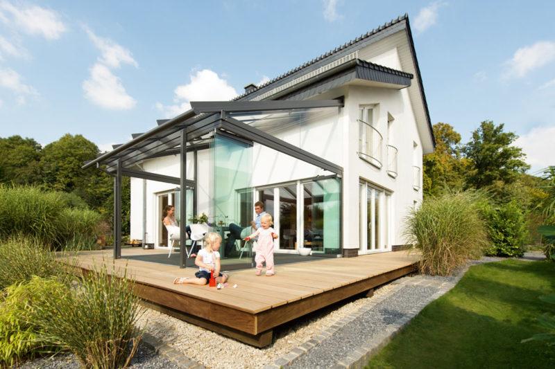 Weißes Einfamilienhaus mit hölzerner Terrasse und Glashaus, eltern und zwei spielende Kleinkinder