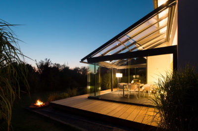 Glashaus auf Holzterrasse, links eine kleine Feuerschale und Gebüsch dahinter