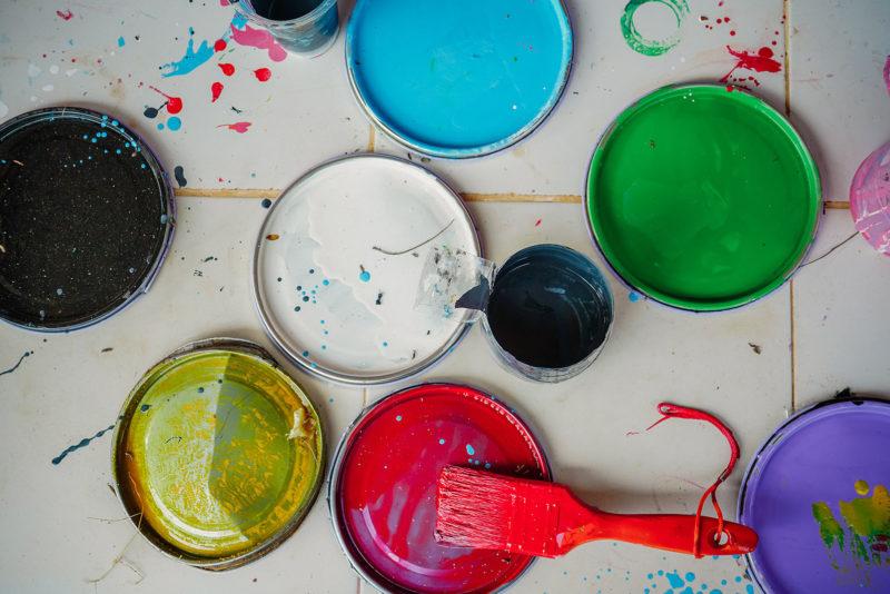 Pinsel und Eimer mit verschiedenen Farben von oben gesehen
