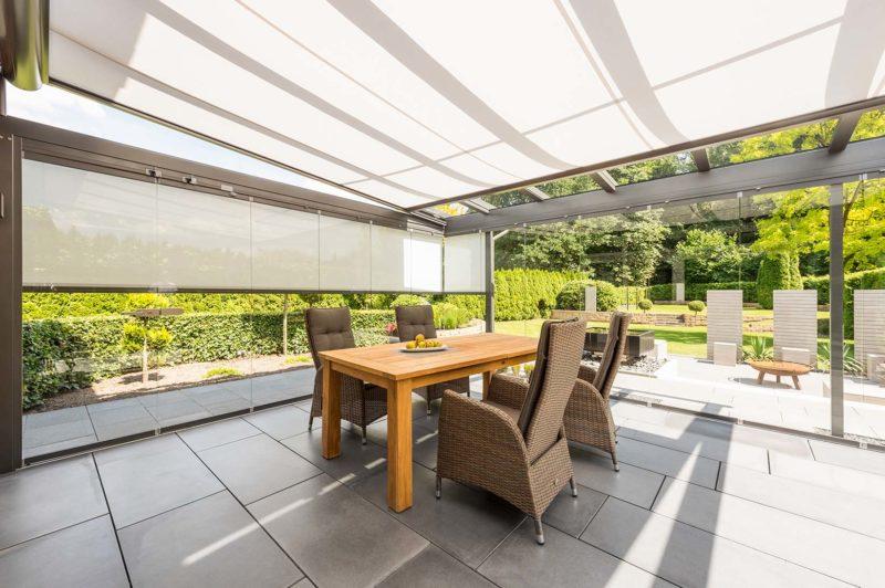 Innenansicht Glashaus mit Ober- und Seitenmarkise, mittige Sitzgruppe