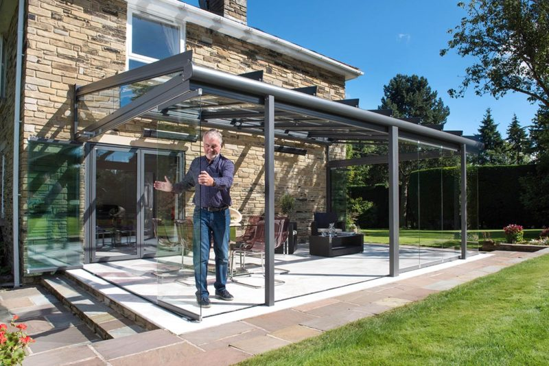 Älterer Mann bewegt ein Glaselement in einem Glashaus