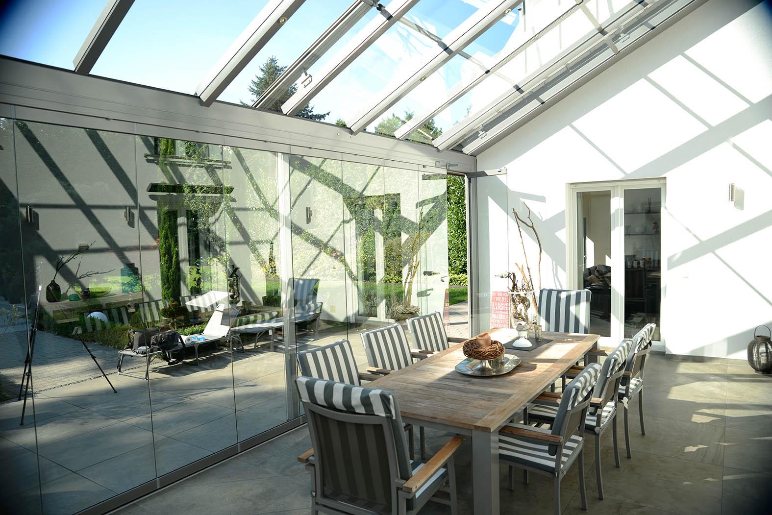 Glashaus von innen mit Essgruppe.