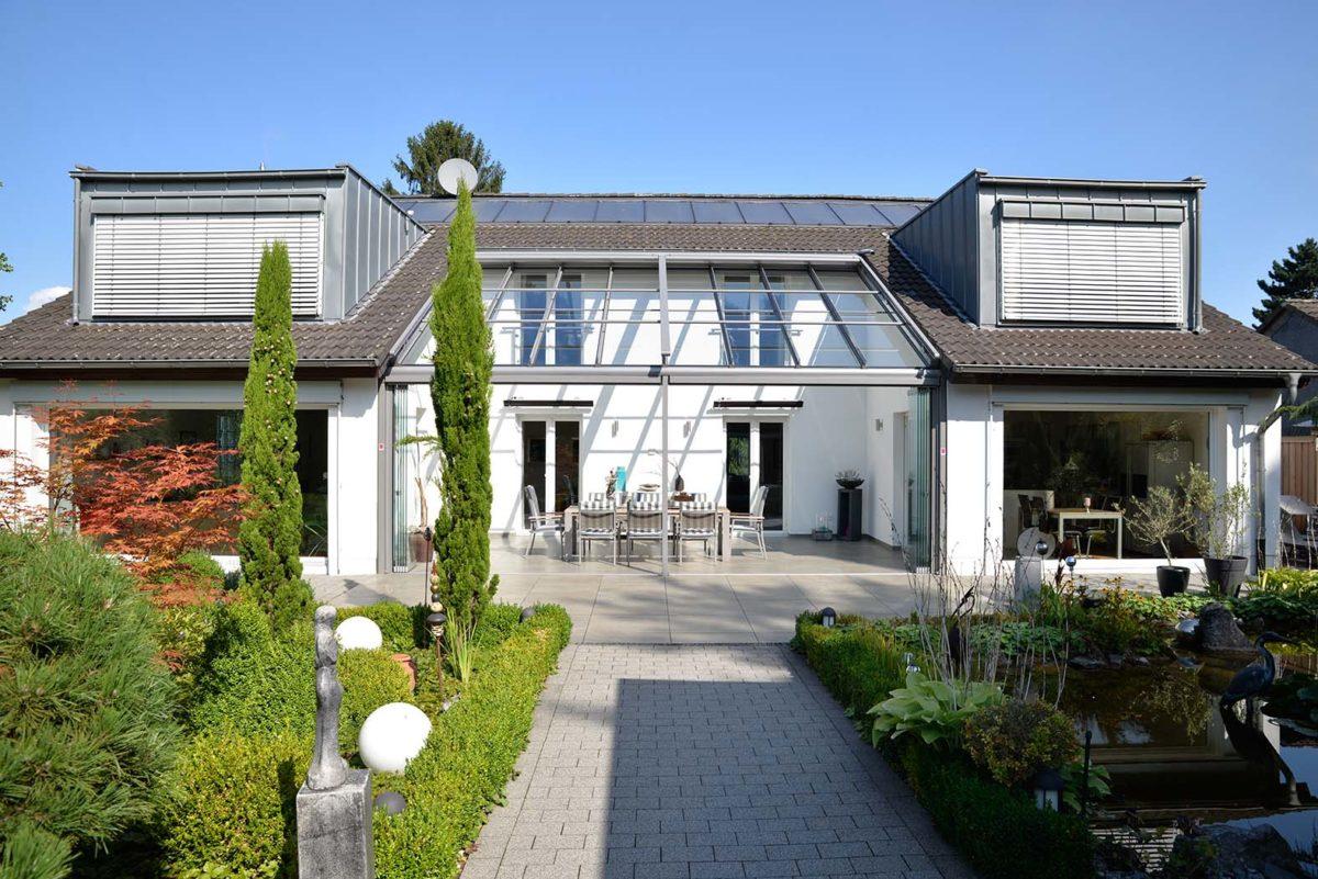Einfamilienhaus mit Glashaus zwischen zwei Flügeln