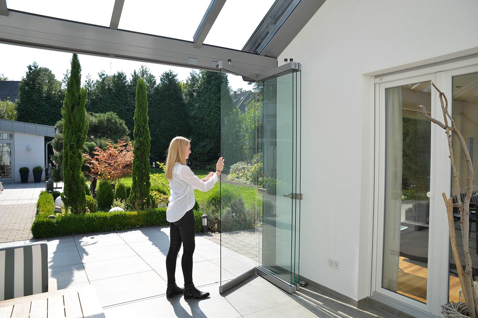 Frau schiebt gläserne Seitenelemente eines Glashauses zusammen.