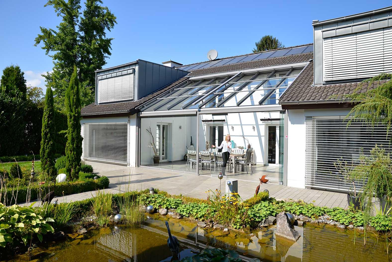 Einfamilienhaus mit Garten udn Glashaus, das zwischen zwei Hausflügeln liegt.