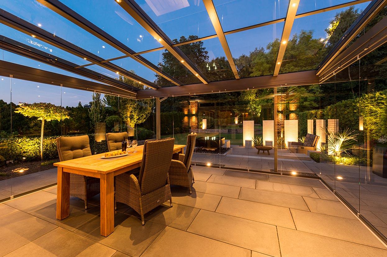 Glashaus von innen mit Beleuchtung und Essgruppe