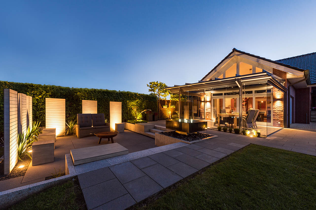 Außenansicht Einfamilienhaus am Abend mit Glashaus und beleuchtetem Garten.