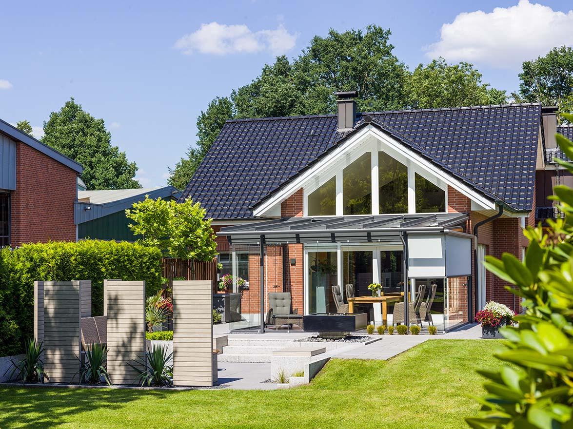 Außenansicht Einfamilienhaus mit Glashaus und Garten bei Tag.