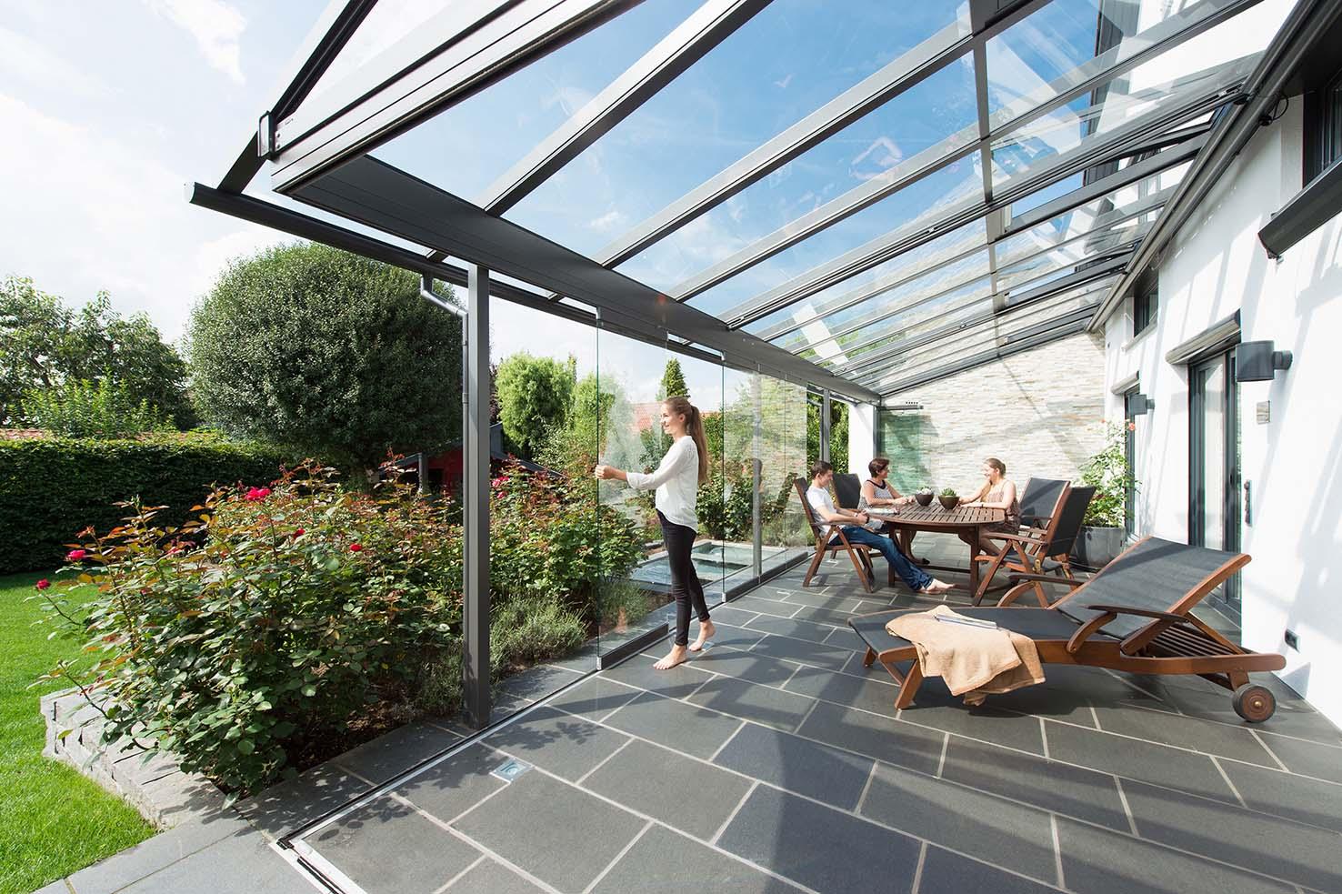 Terrassenüberdachun mit junger Frau, die Glaselemente verschiebt